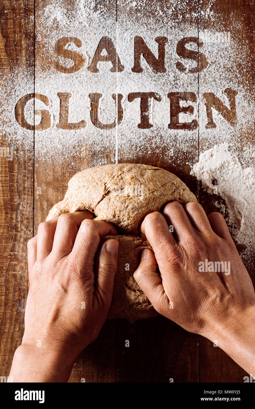high-angle shot of a young man kneading a piece of dough on a wooden table sprinkled with a gluten free flour where you can read the text sans gluten, - Stock Image