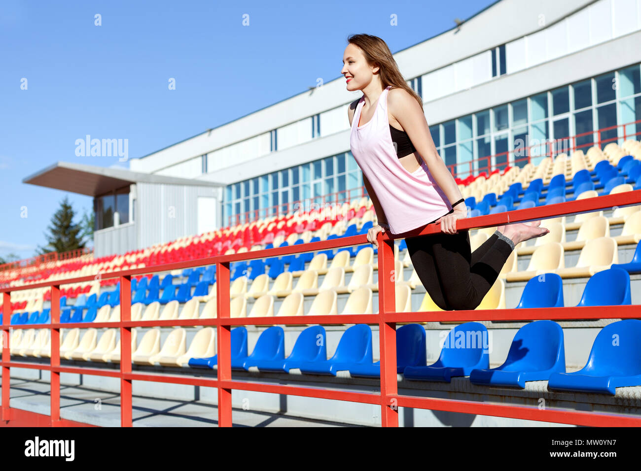 Young woman in sportswear standing on the stadium podium. - Stock Image