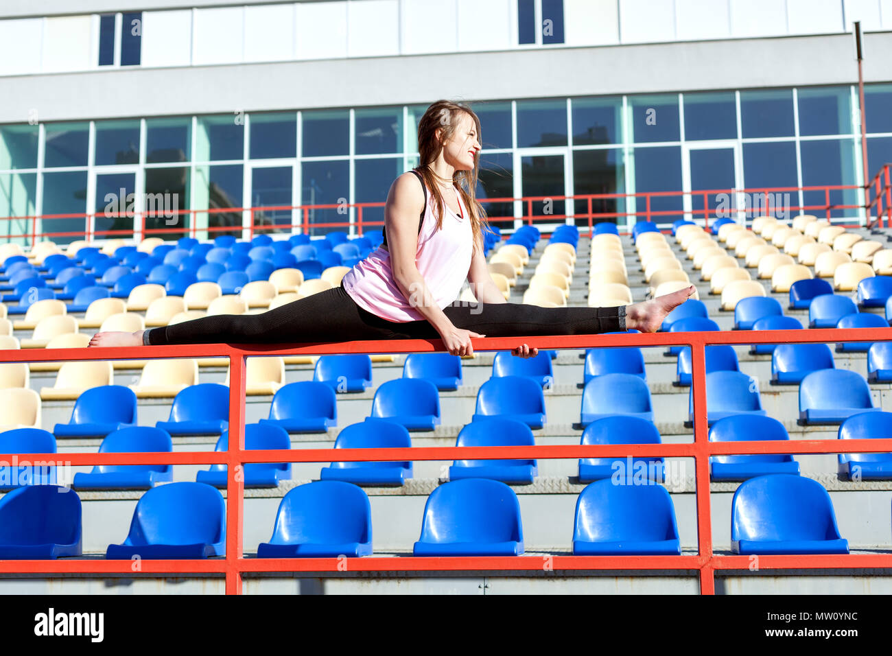 Young woman sitting on a twine on the fence of the stadium podium. - Stock Image