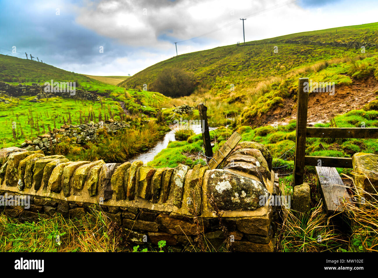A stile on the rolling green walking hills of Derbyshire - Stock Image