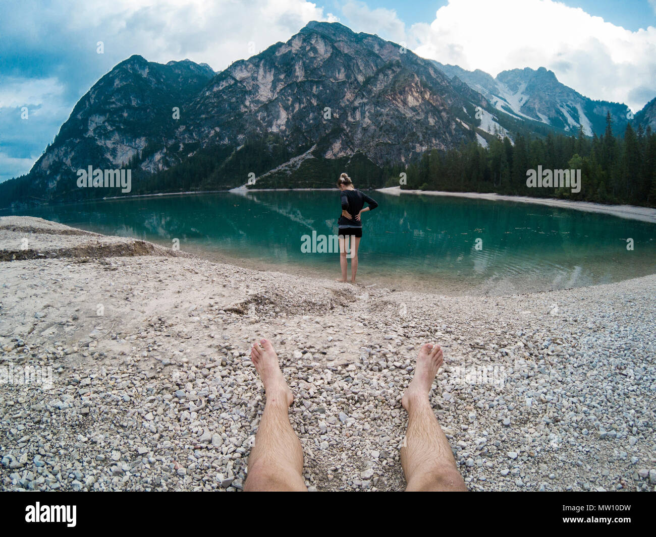 Mans legs and women standing against amazing view of Braies Lake Lago with  mountains reflected in lake water Dolomites Alps 7d7c062e7f