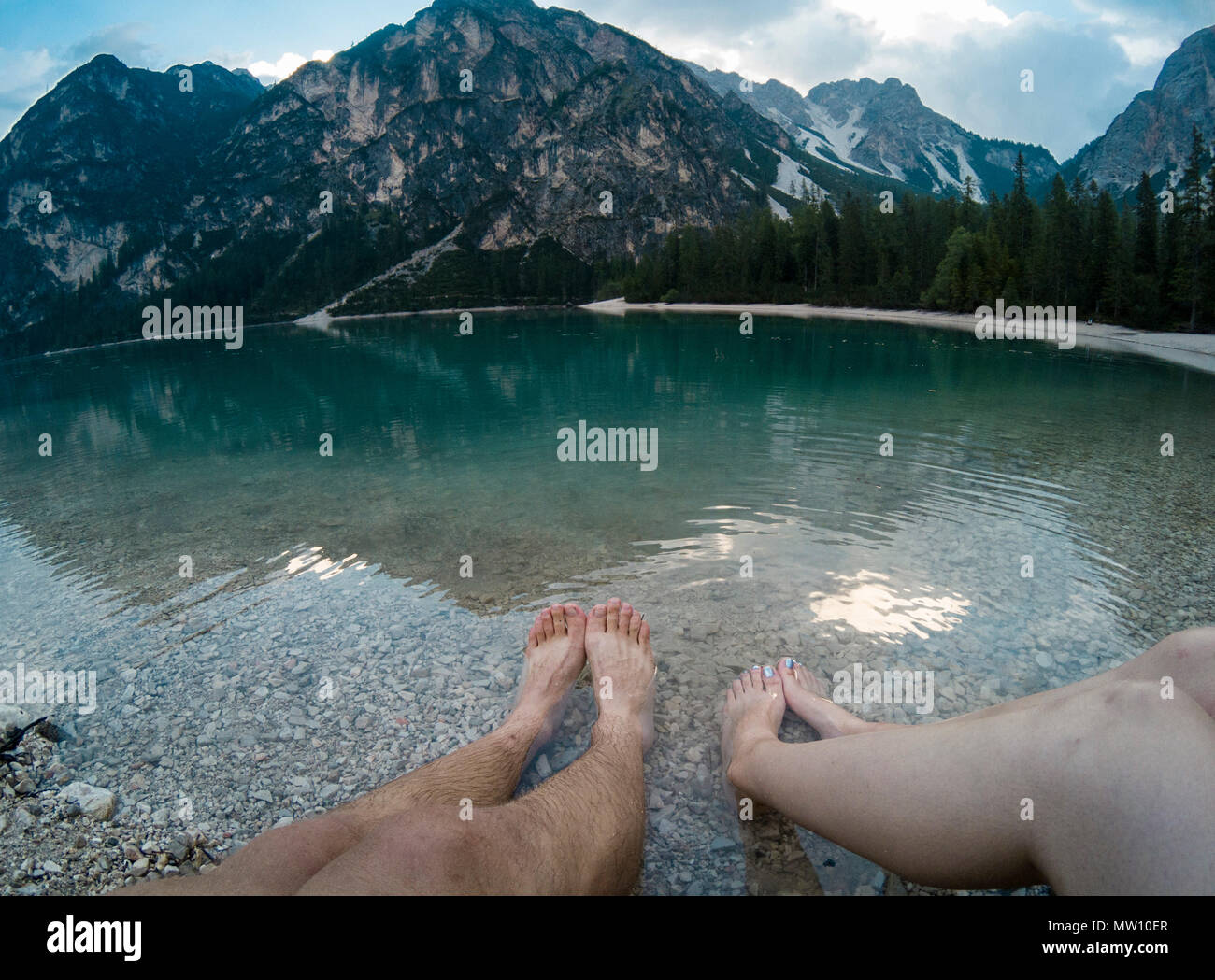 Mans and womens leg against amazing view of Braies Lake Lago with forest  and mountains reflected in lake water Dolomites Alps 5aded104ba