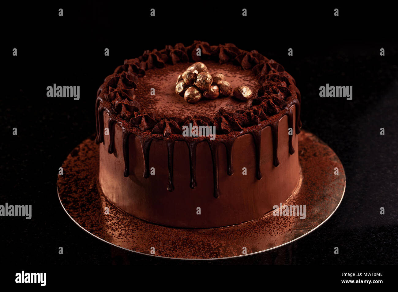 Chocolate cake with nuts on a black background - Stock Image