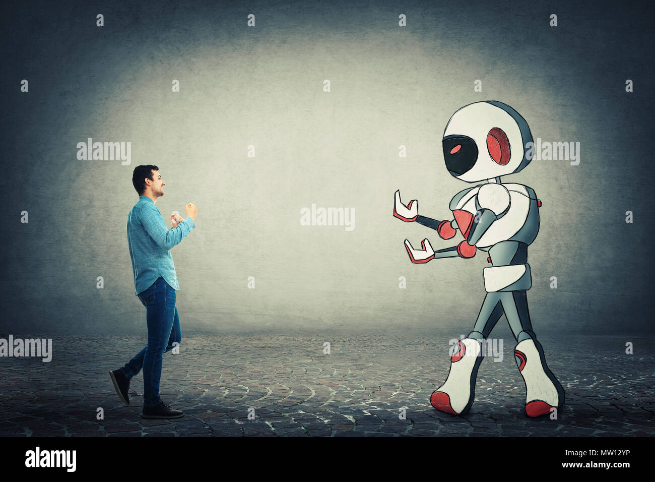 Young businessman holding fists ready to fight against robot. Rivalry between human and technology. Danger of losing the job, replacing the human work - Stock Image