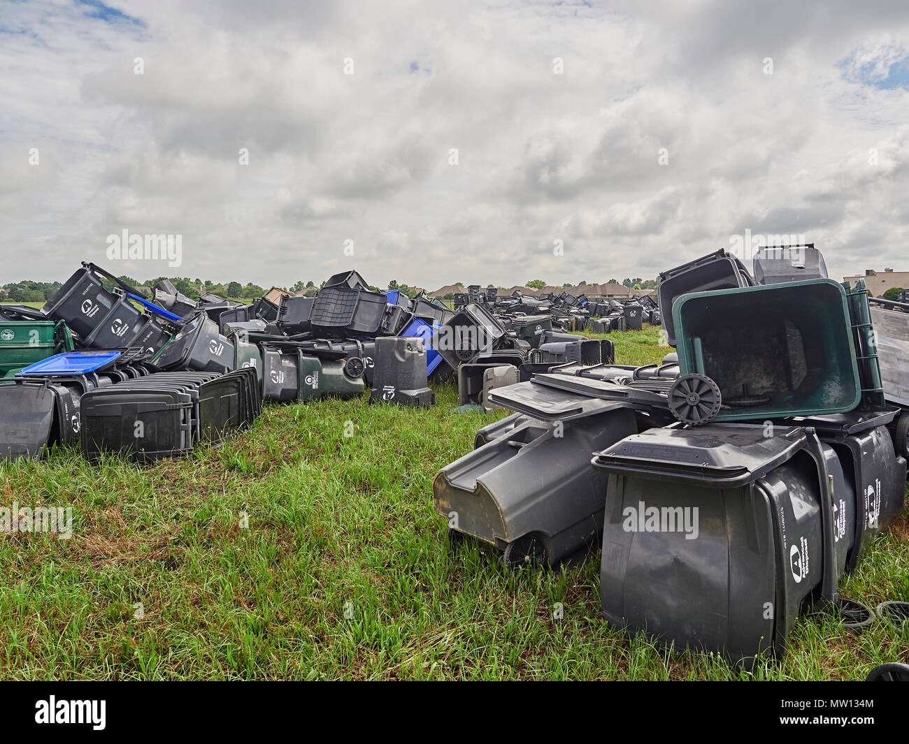 Large plastic trash cans discarded and piled or stacked in a field waiting for removal in Pike Road Alabama, USA. - Stock Image