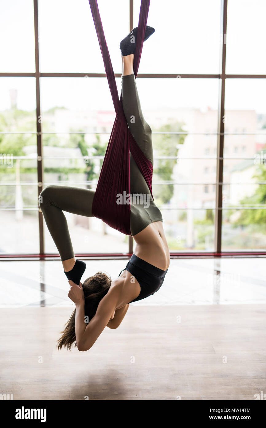 Fit young woman doing fly yoga stretching exercises in fitness training at gym hall . Sport and healthy lifestyle concept. Stock Photo