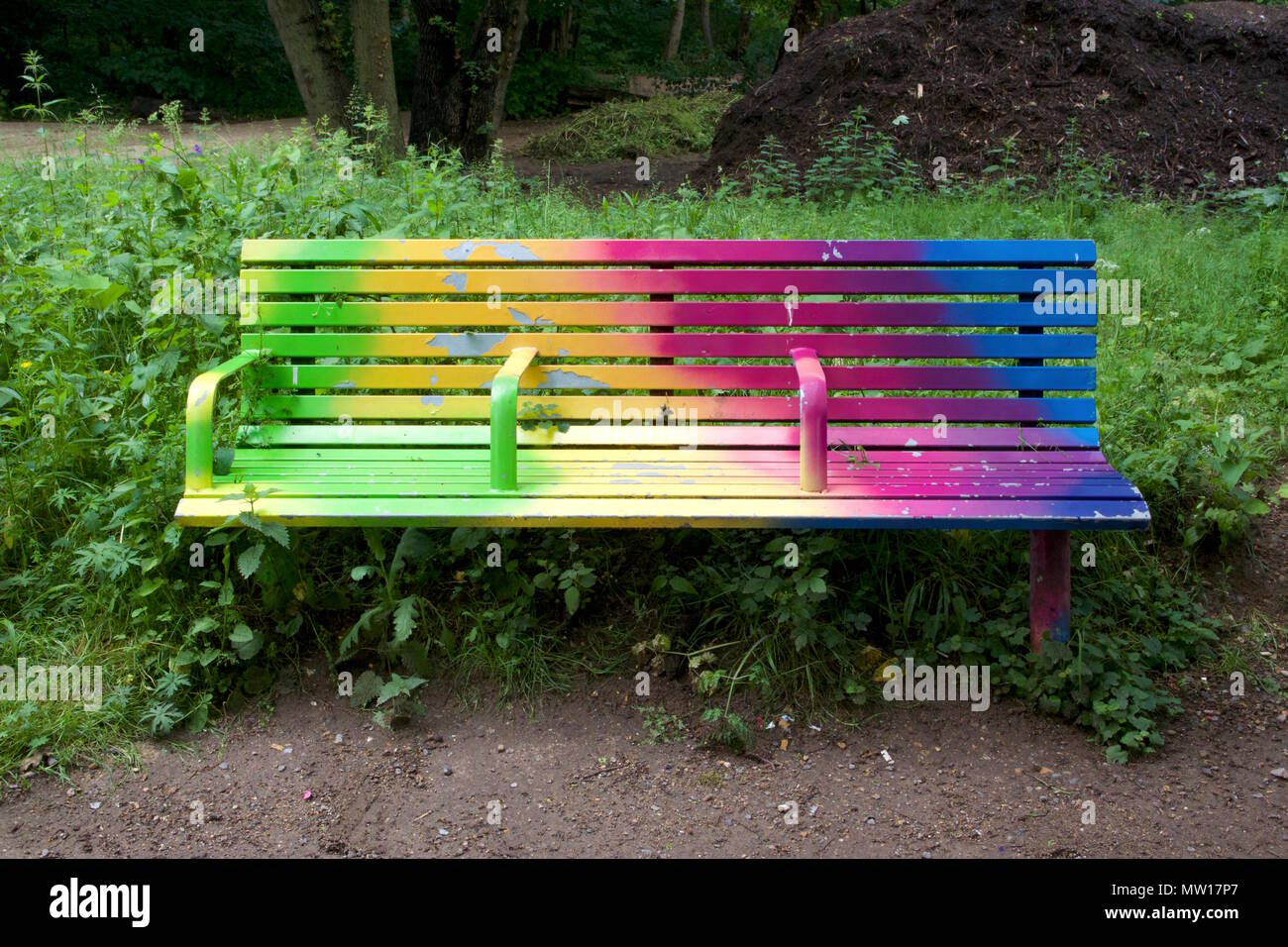 A rainbow coloured bench called Gradient Fade by Adham Faramawy in Tower Hamlets Cemetery Park - Stock Image