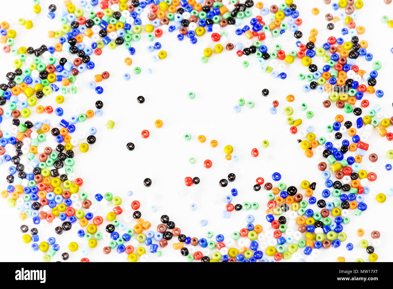 Many multi-colored beads for needlework are scattered on a white ...
