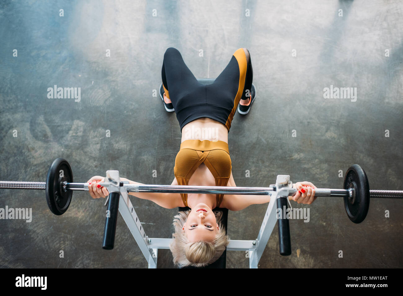 overhead view of young athletic woman weightlifting barbell at gym - Stock Image