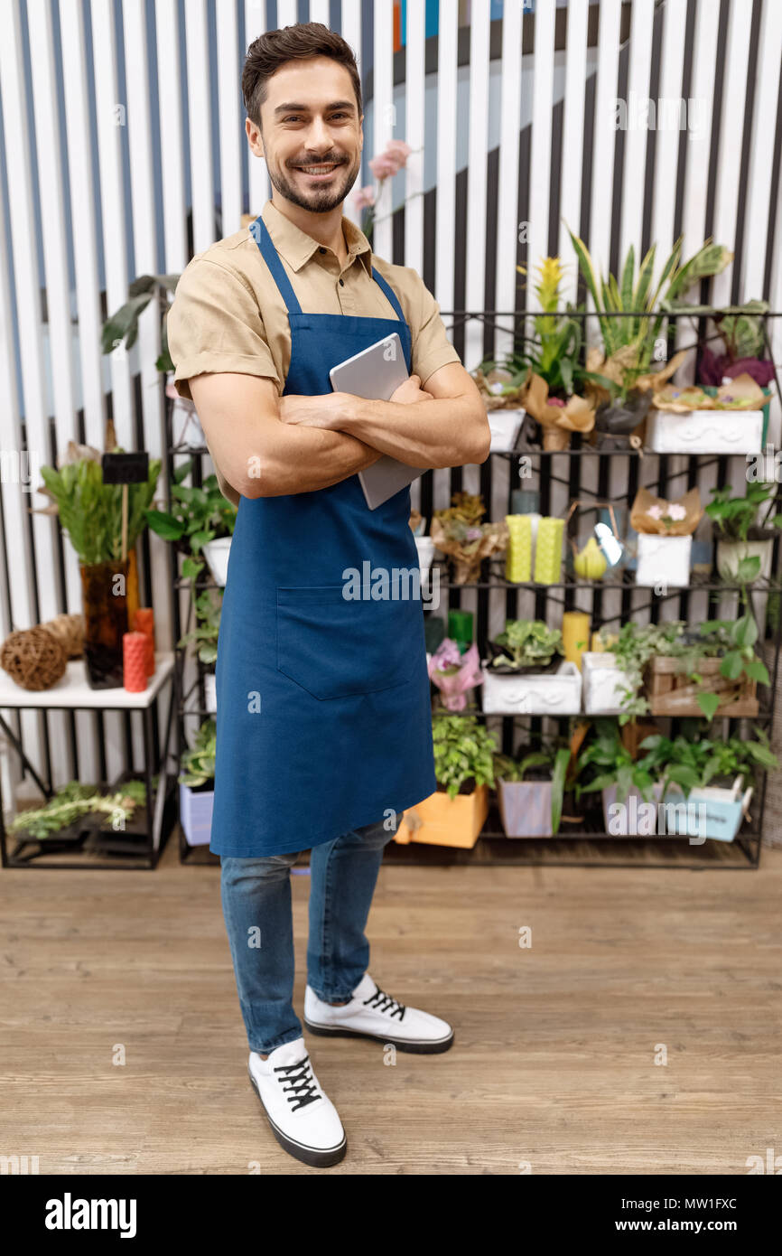 handsome young florist in apron holding digital tablet and smiling at camera in flower shop - Stock Image