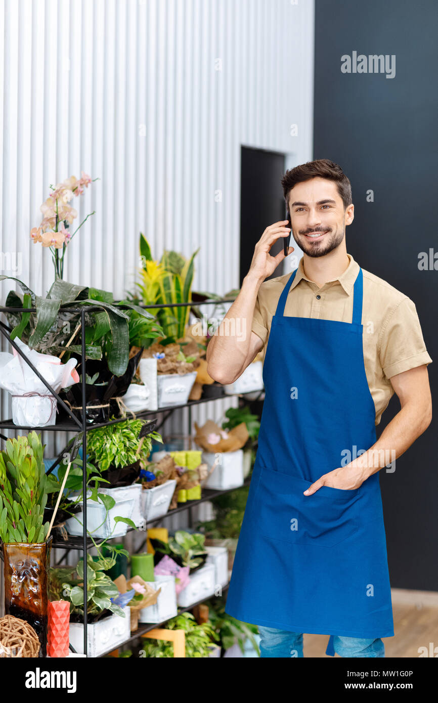 handsome smiling male florist talking on smartphone while working in flower shop - Stock Image