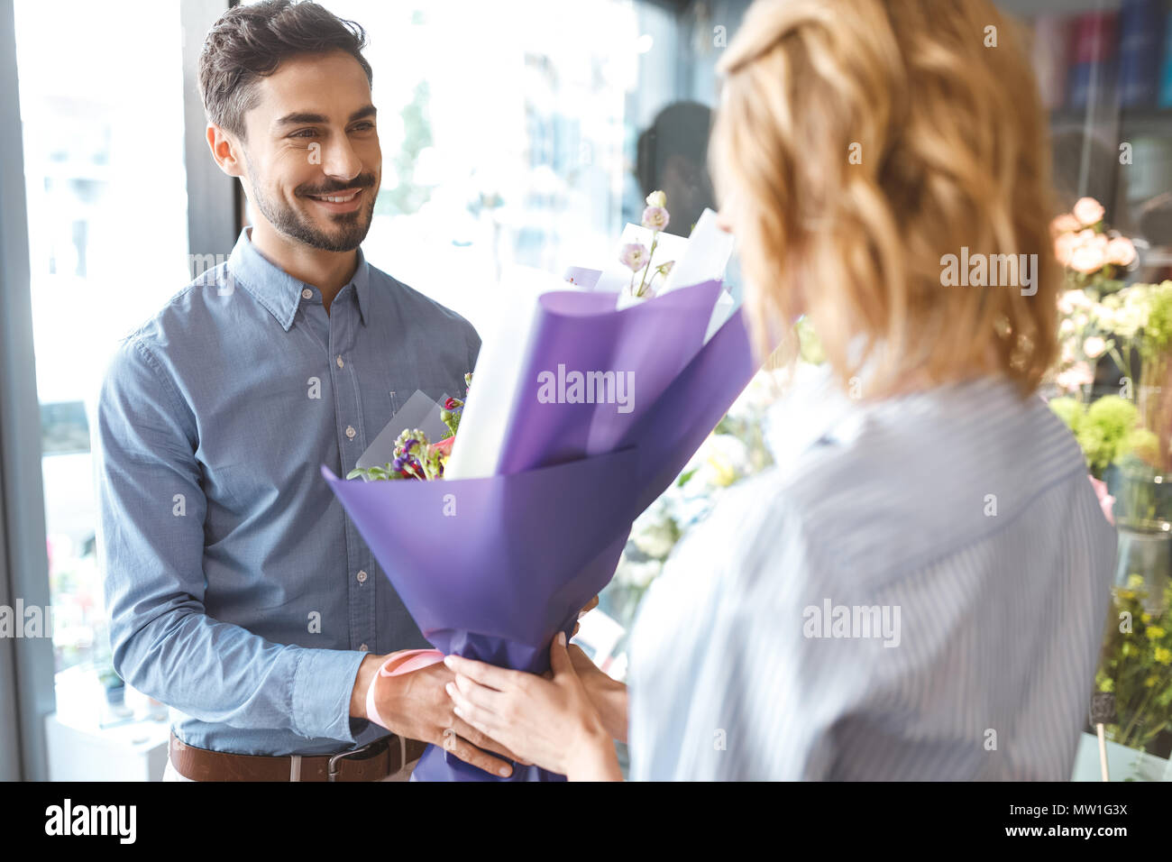 young female florist giving beautiful bouquet to smiling buyer in flower shop - Stock Image