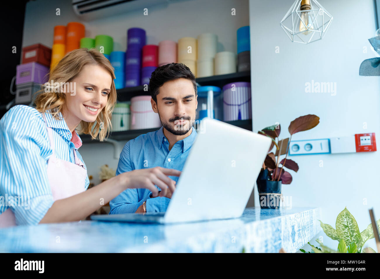 smiling young florist and male buyer using laptop together in flower shop - Stock Image