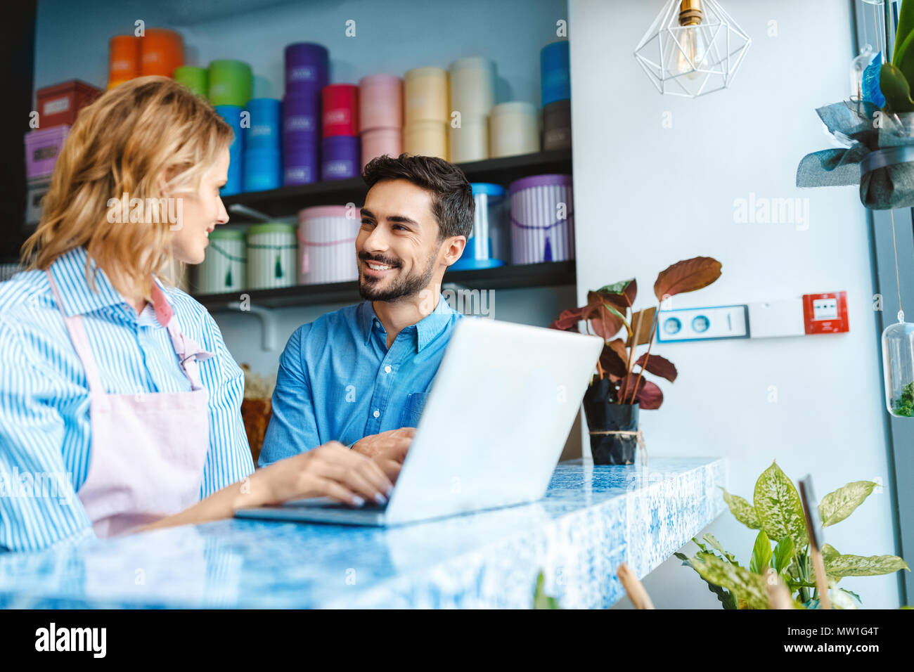 attractive florist and handsome buyer using laptop and smiling each other in flower shop - Stock Image