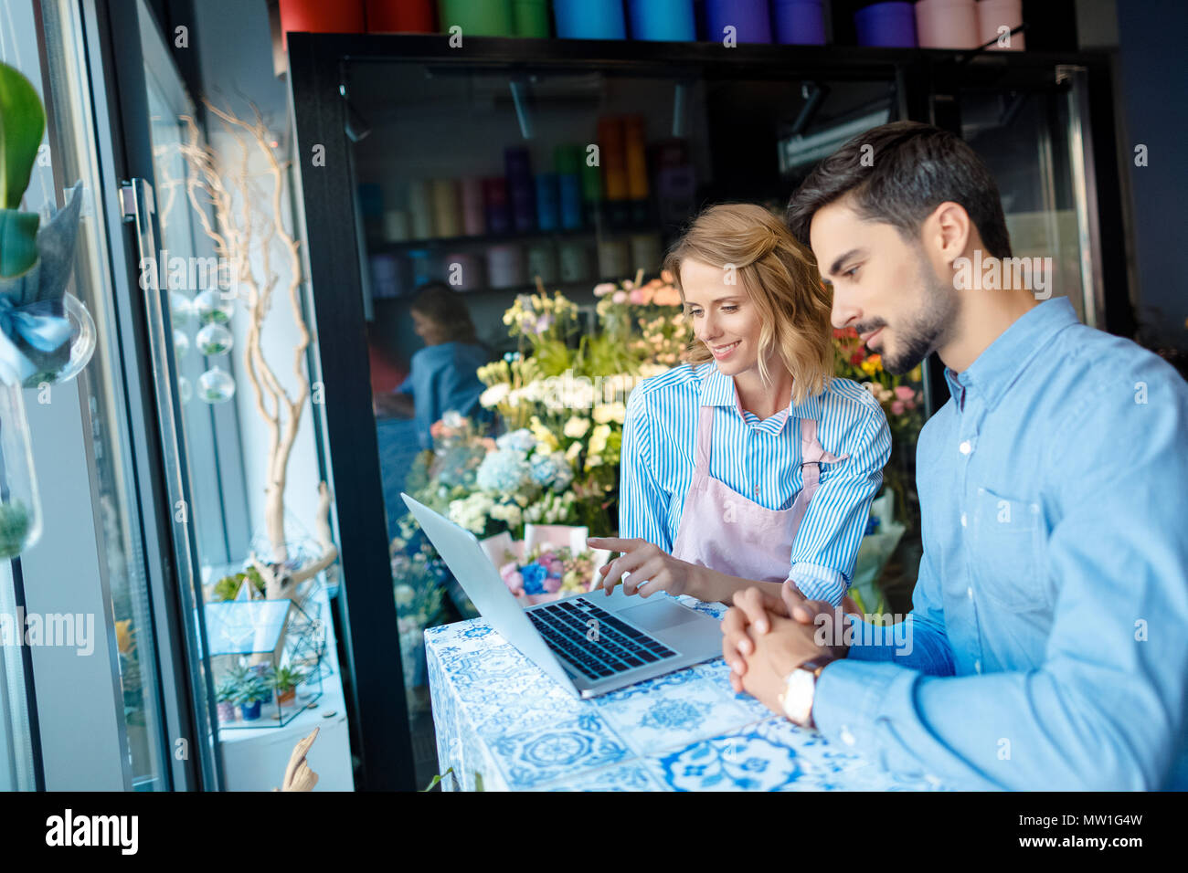 side view of young florist and buyer using laptop in flower shop - Stock Image
