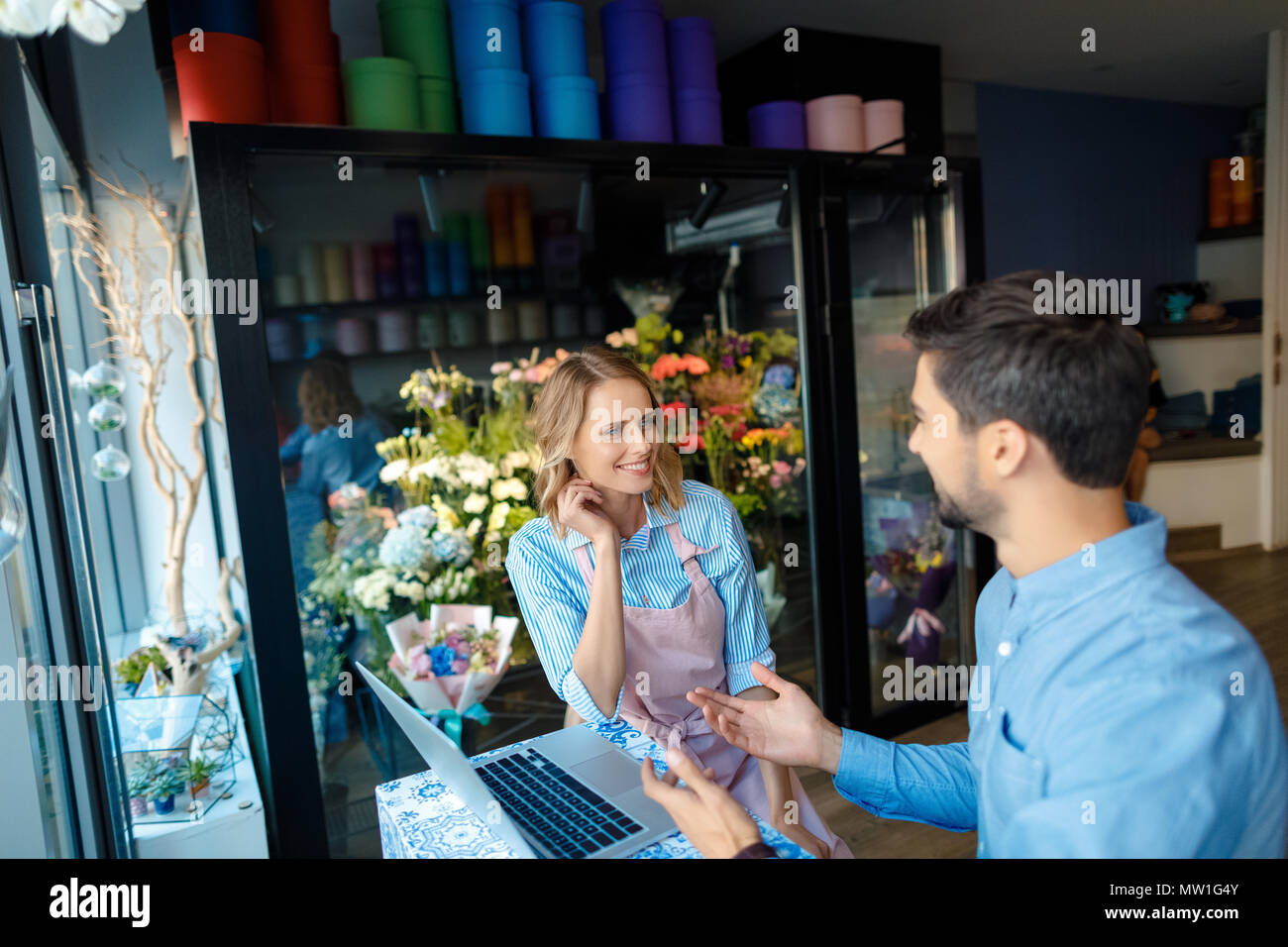 attractive young florist and buyer using laptop and smiling each other in flower shop - Stock Image
