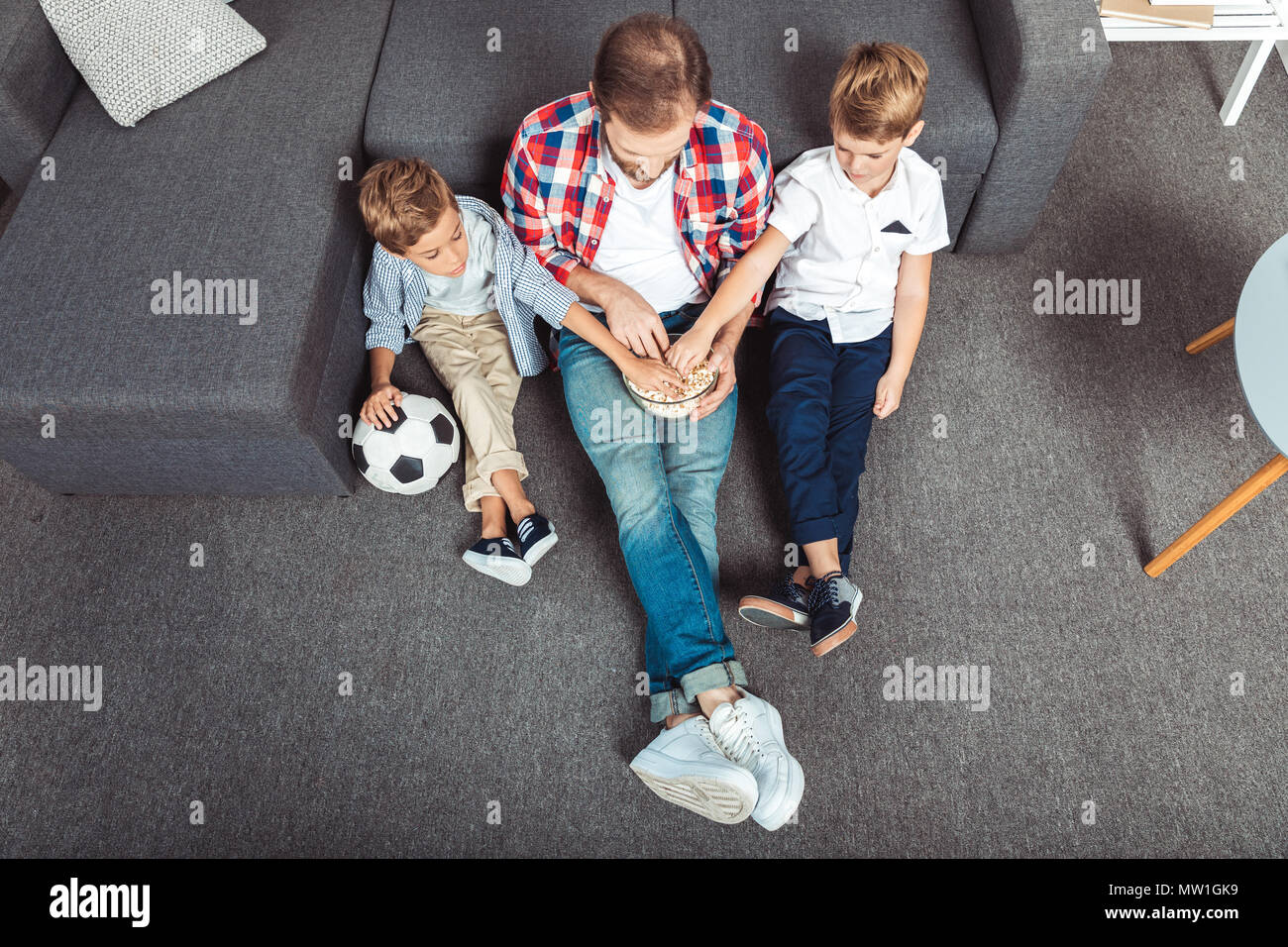 high angle view of father with sons eating popcorn while watching soccer match at home - Stock Image