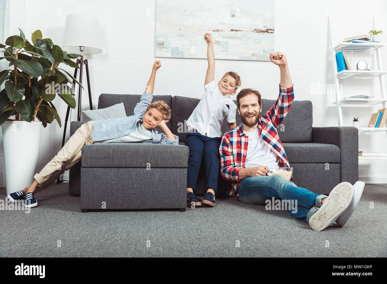 happy father with sons raising hands and eating popcorn at home - Stock Image