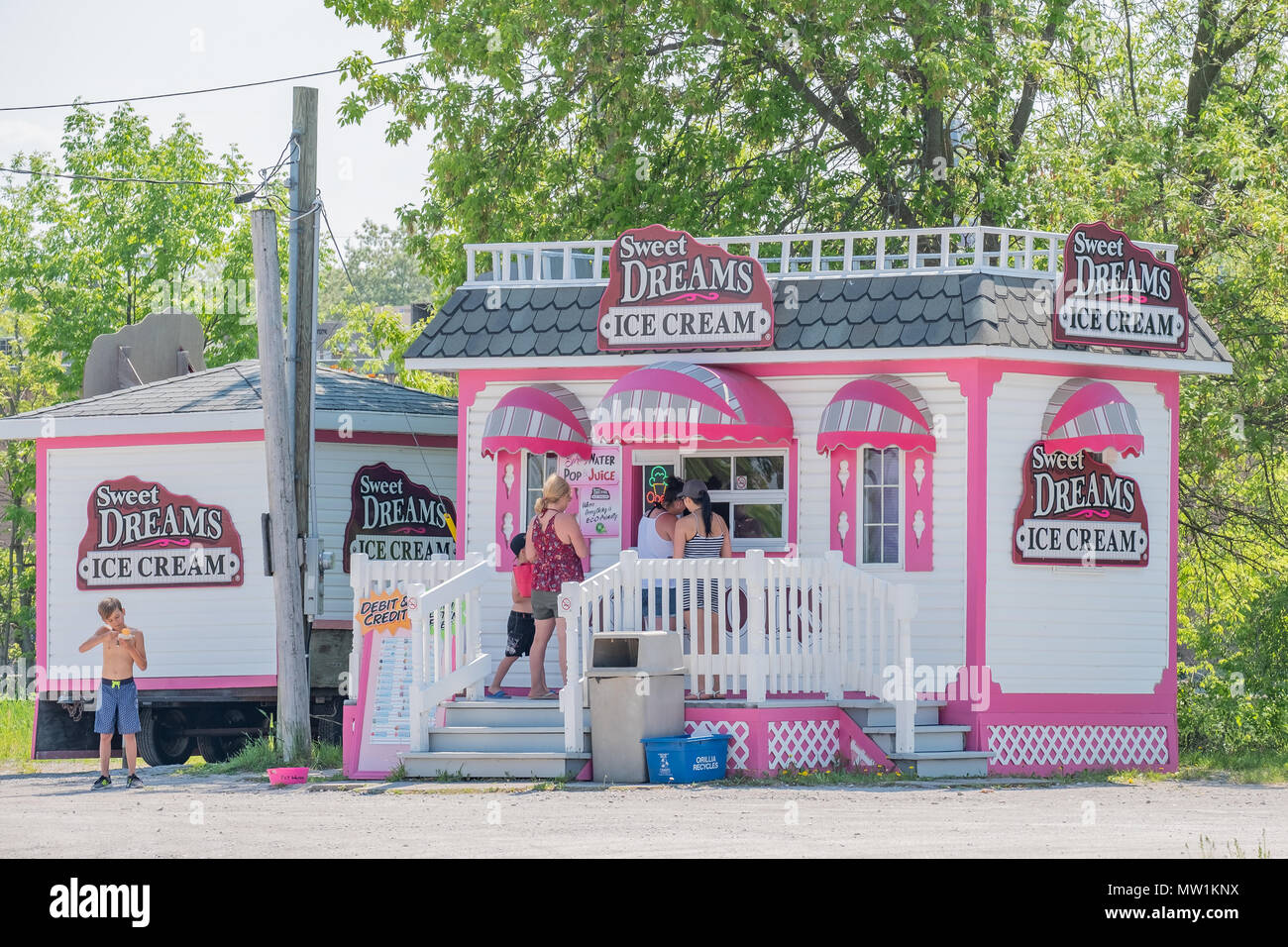 People ordering ice cream on a hot day from a shop on the Orillia Ontario Canada lakefront. - Stock Image