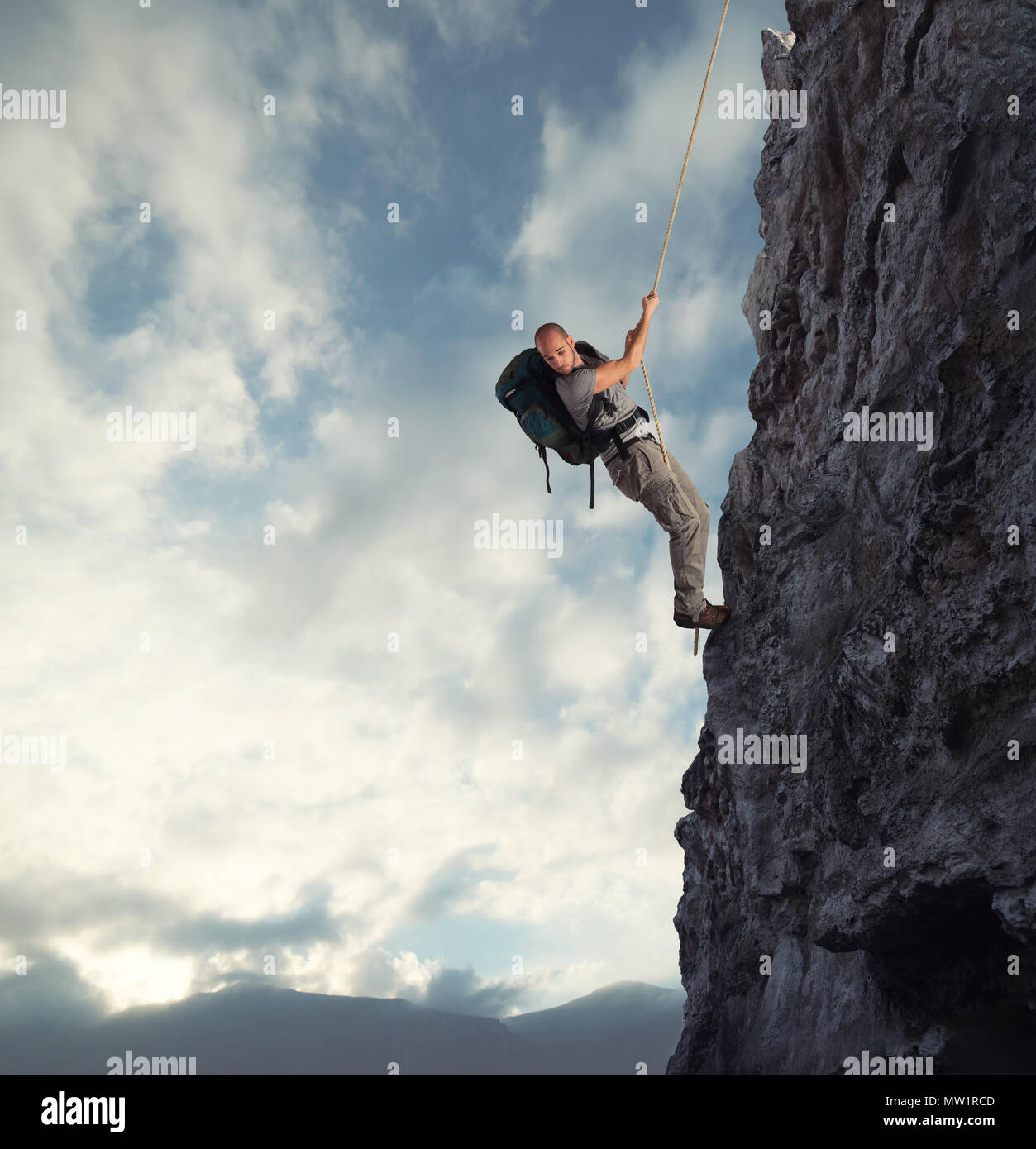 Man climbs a high danger mountain with a rope - Stock Image