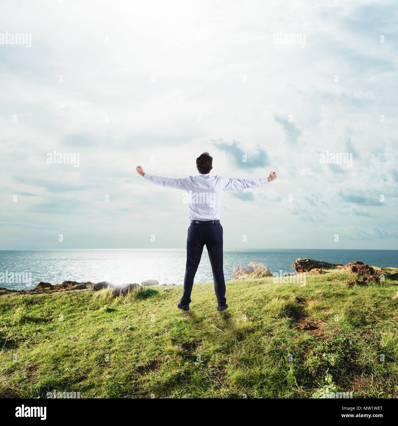 Businessman with open arms to the sky. concept of success and freedom - Stock Image