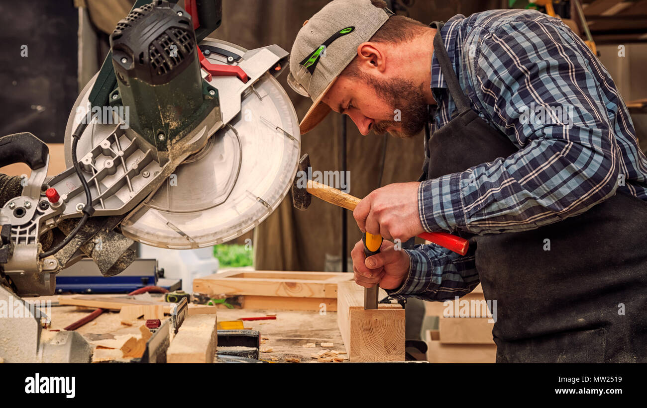 Carpenter work with circular saw for cutting boards, the man