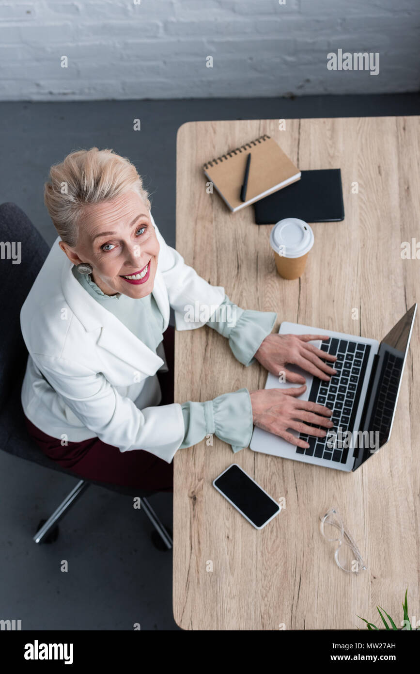 overhead view of smiling senior businesswoman using laptop at workplace - Stock Image