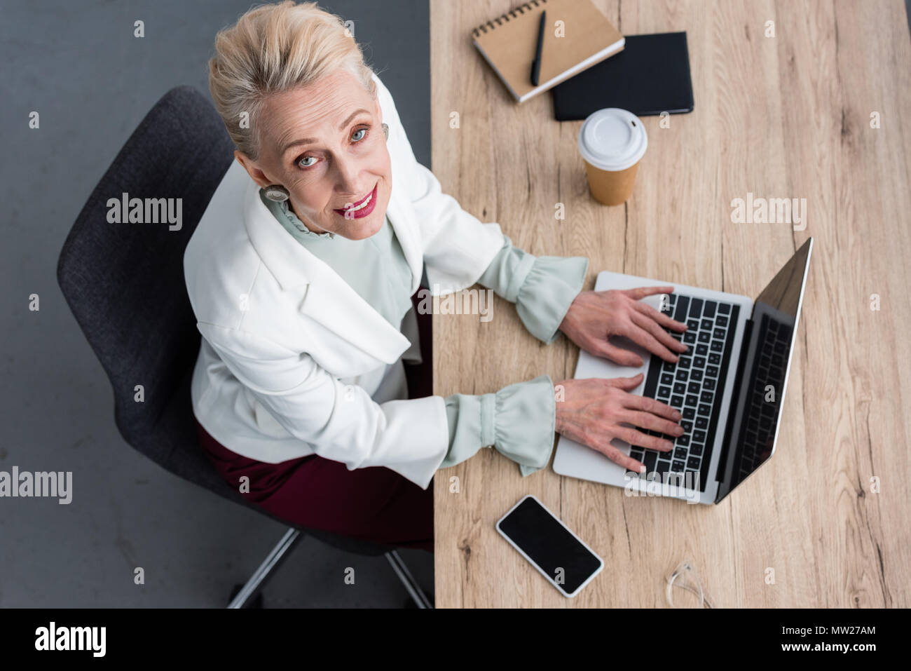 overhead view of elegant business woman working with laptop in modern office - Stock Image