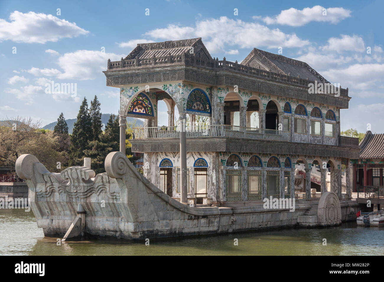 Beijing, China - April 29, 2010: Summer Palace. Closeup of gray marble pleasure boat with a few painted decorations docked at lake. Under blue sky wit - Stock Image