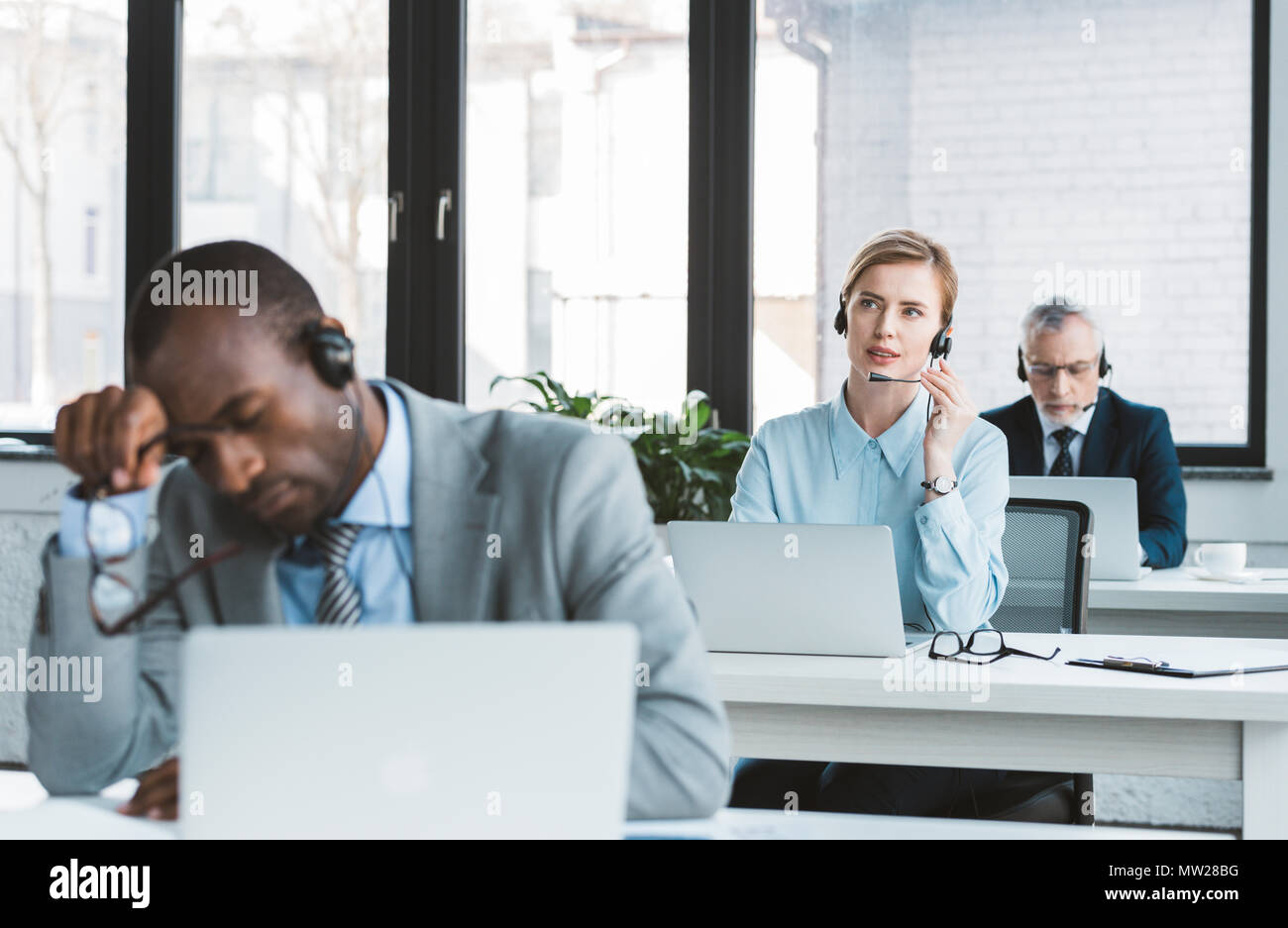three multiethnic business people in headsets working with laptops in modern office - Stock Image