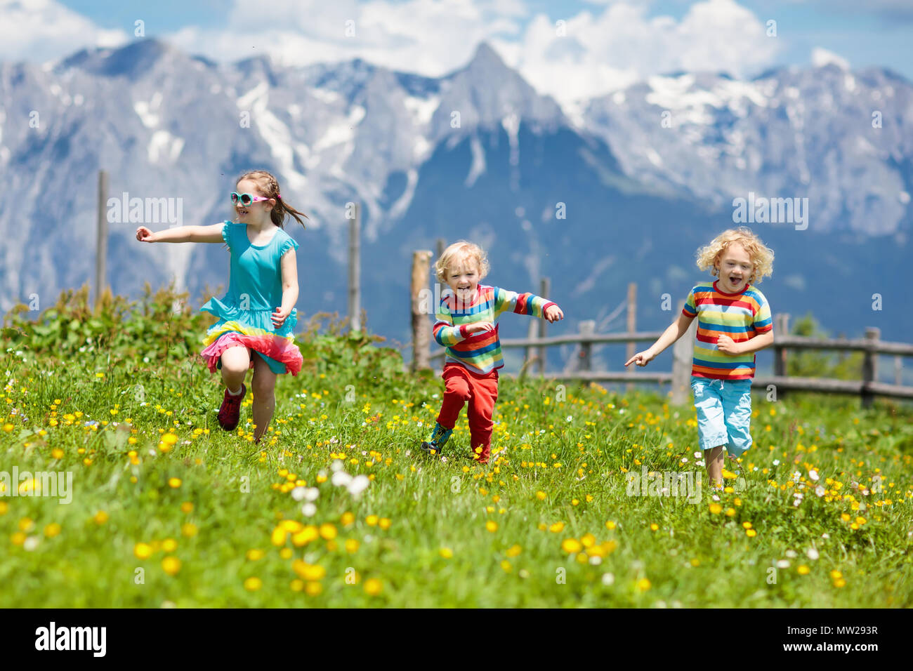 Children Hiking In Alps Mountains Kids Run At Snow Covered Mountain Austria Spring Family Vacation Little Boy And Girl On Hike Trail Blooming