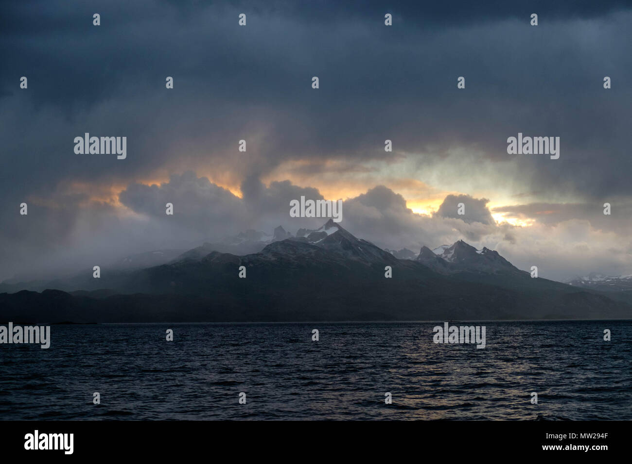Thanks to an opening in the dark clouds, the sun shows its last fire of the day behind the mountains of the Beagle Channel, Chilean part. - Stock Image