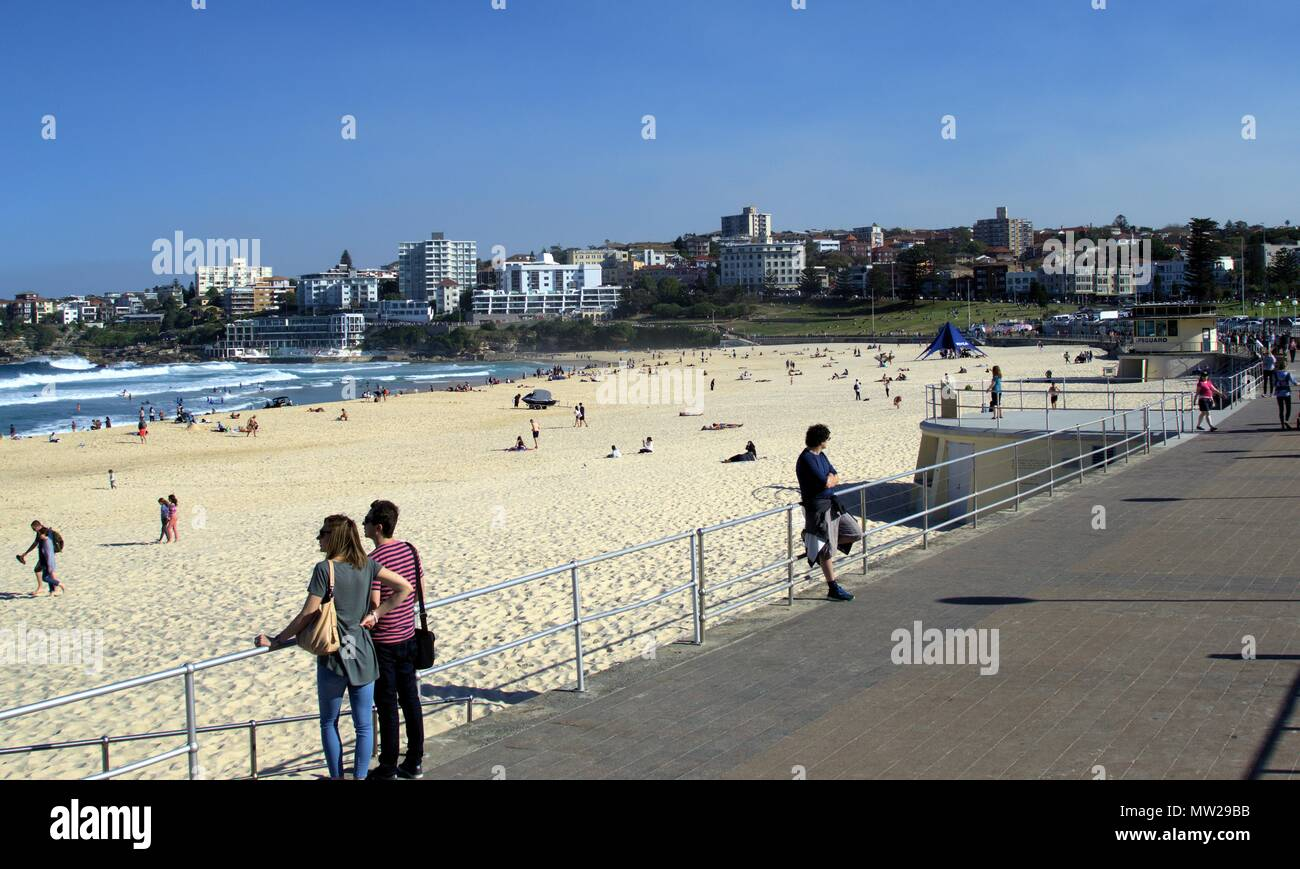 People enjoying sunny day at Bondi beach Sydney Australia. In view is Sydney cityscape of waterfront buildings or real estate in south side of Bondi - Stock Image