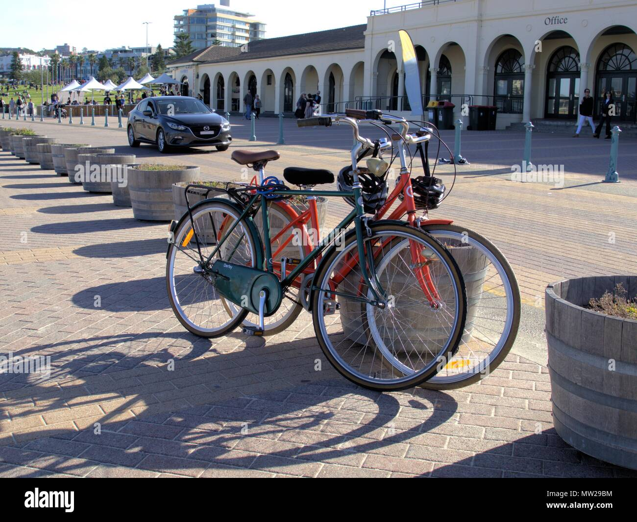 Bicycles parked by the street called Queen Elizabeth Dr at Bondi beach in Sydney, Australia. Moving car, people and front of Bondi Pavilion. - Stock Image