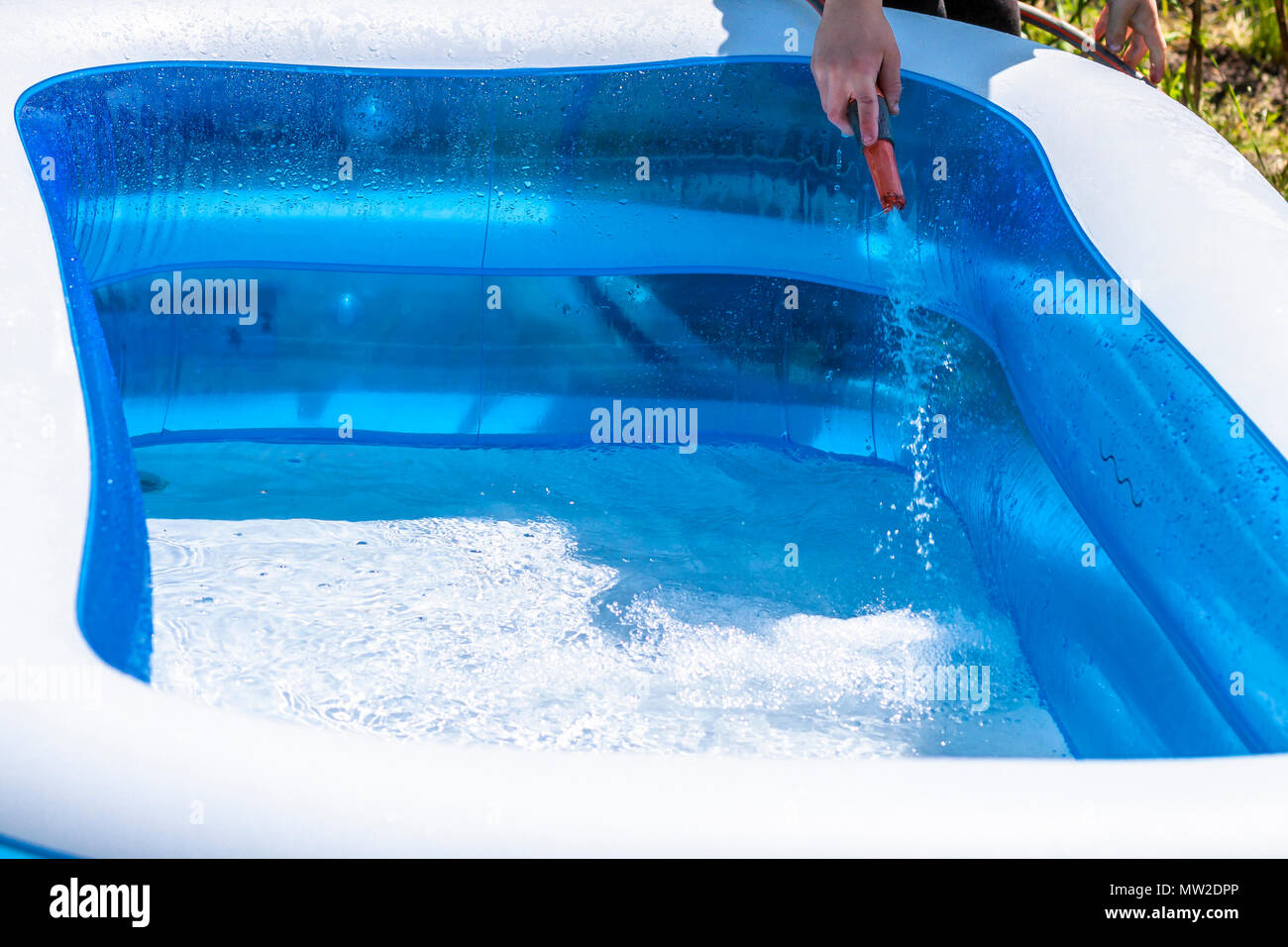 Little boy filling filling swimming pool with water Stock ...