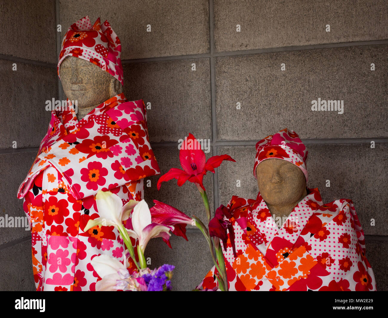 Buddhist statues, at a roadside shrine, robed in unusual patterned fabric, with flower offerings, Takamatsu, Shikoku, Japan - Stock Image