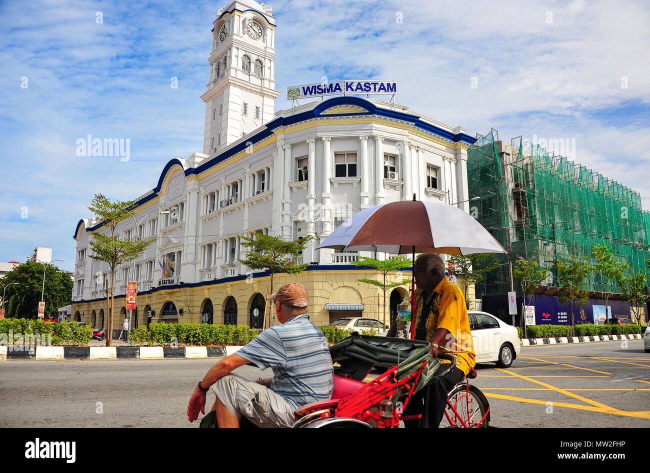 A tourist in a trishaw views the Wisma Kastam (Malayan Railway Building), part of Penang's heritage area. Never a railway station but Customs Offices - Stock Image