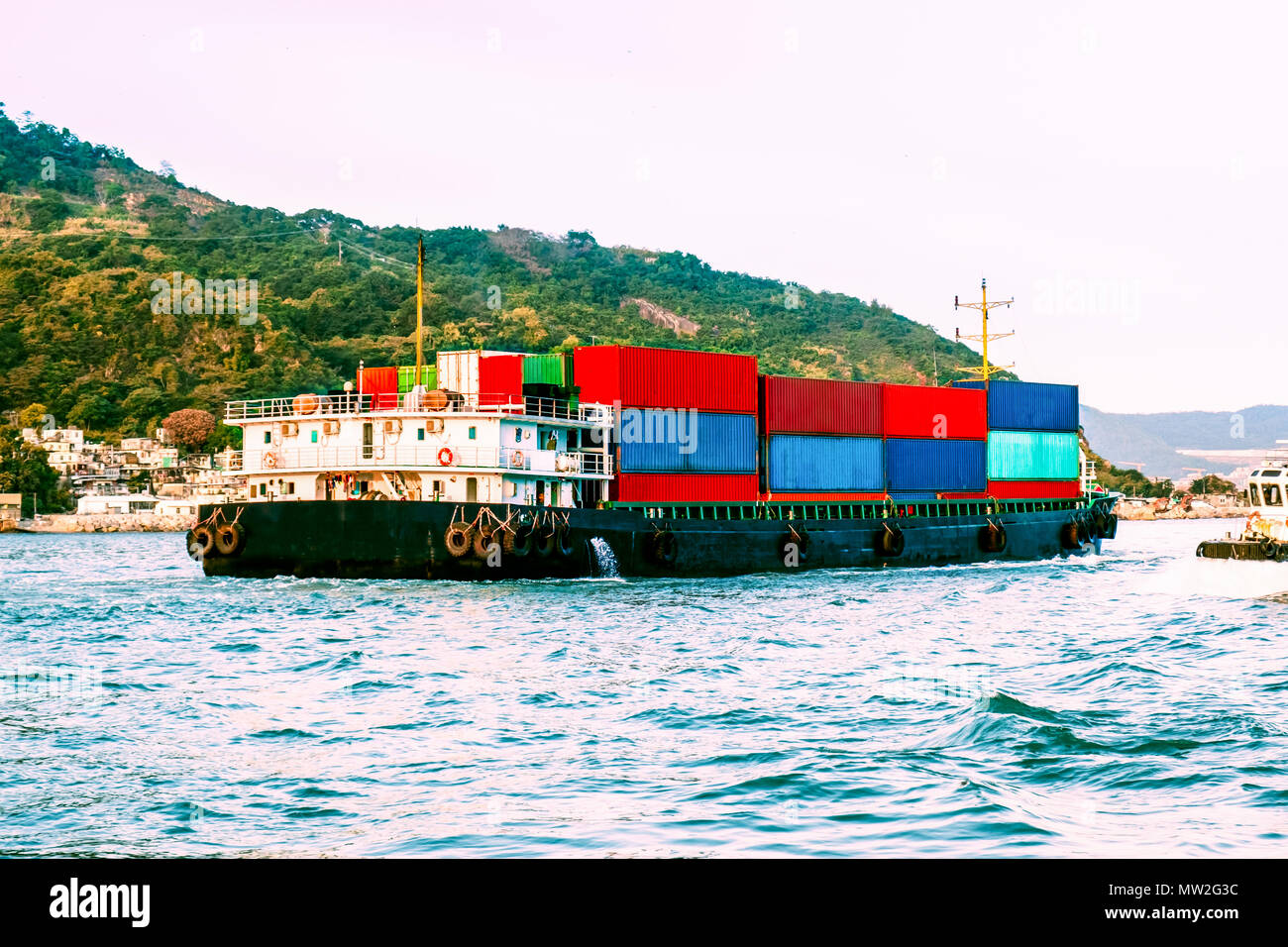 Large cargo nautical vessel in Victoria Harbor, Hong Kong at sunset. Business logistic, import, export concept. South China Sea, Pacific Ocean. Stock Photo