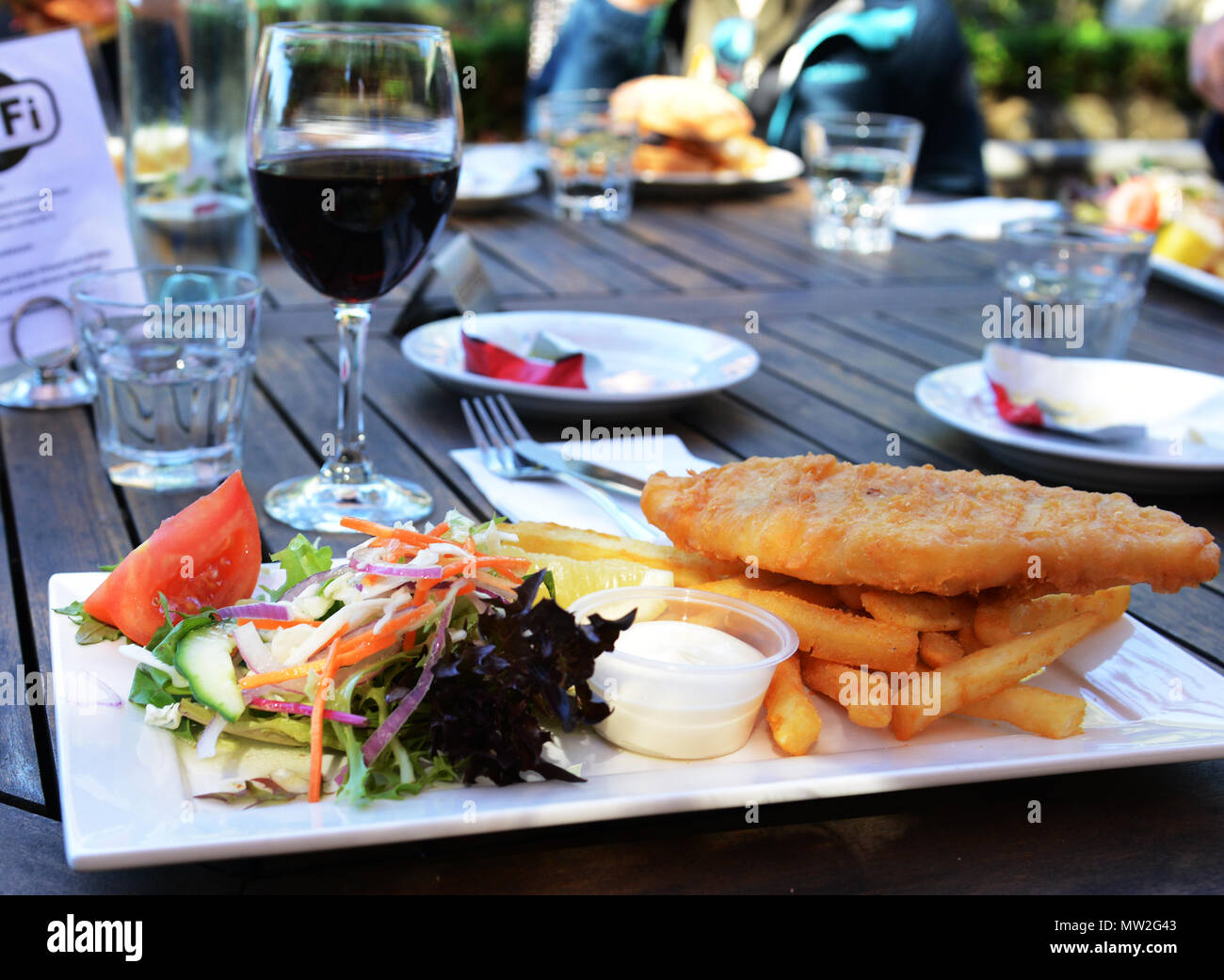 9ff493187b8 A barramundi fish and chips dish served with salad and a glass of red wine.