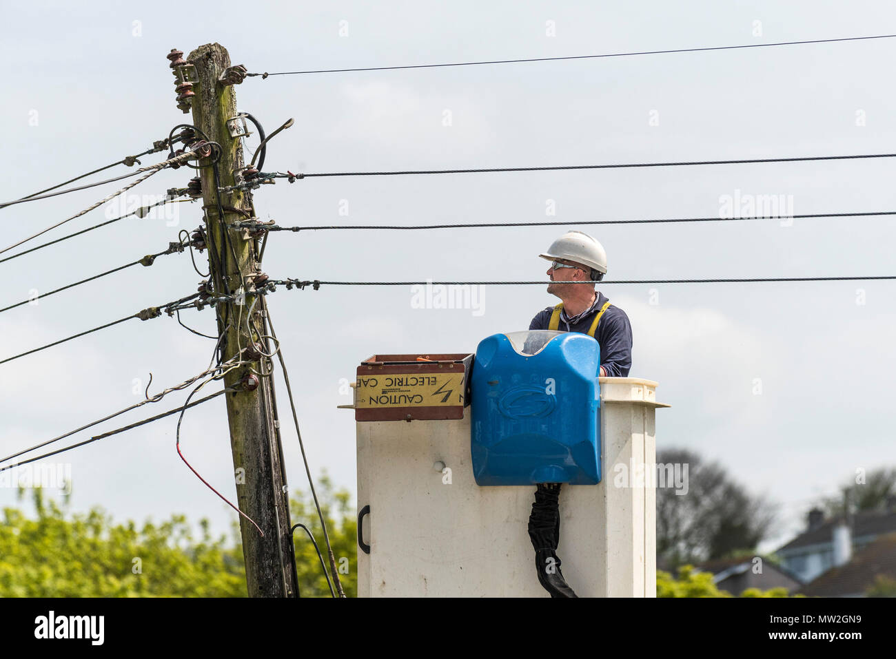 A South West Electricity worker working at height from a cherry picker. - Stock Image