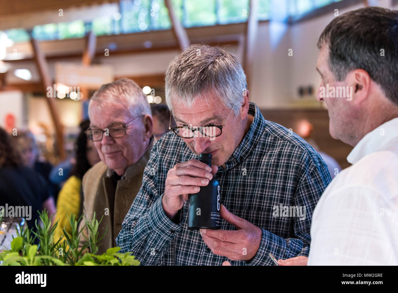 A customer smelling Stafford's Gin at a gin tasting event. - Stock Image