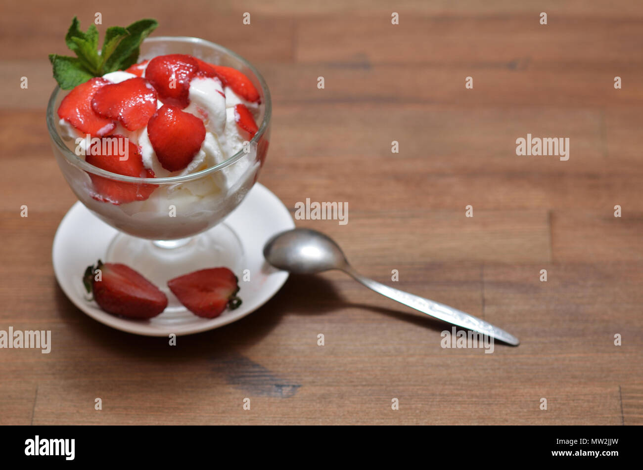 Vanilla ice cream with sliced strawberries and mint in a glass bowl on a white saucer with a teaspoon and halves of strawberries. Stand on a dark wood Stock Photo