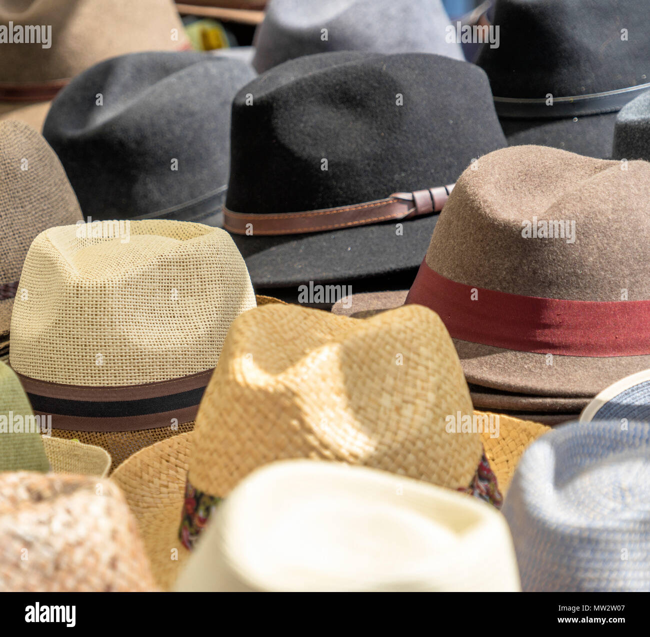 Many hats for men in different shapes and colors in one display for sale, germany - Stock Image