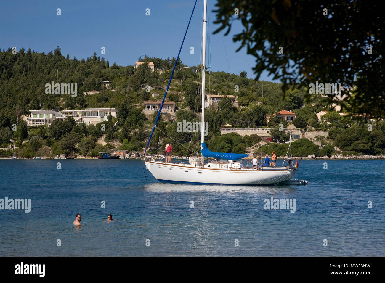 The beach at Moggonissi, at the southern tip of Paxos, Greece: swimmers and an anchored yacht - Stock Image