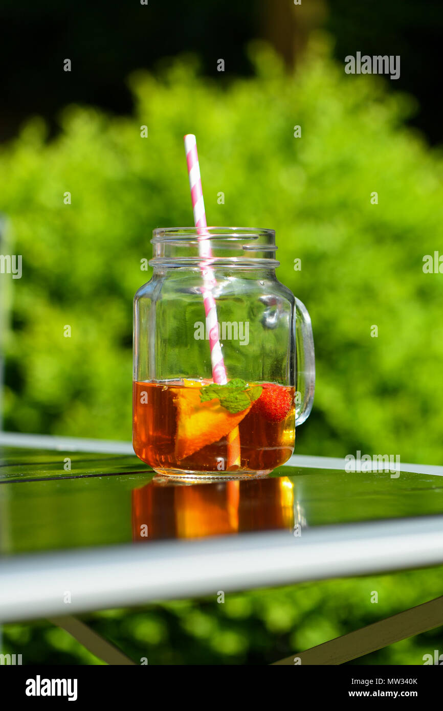 A glass of pimms in a jam jar glass with a paper straw outside on a summers day. - Stock Image