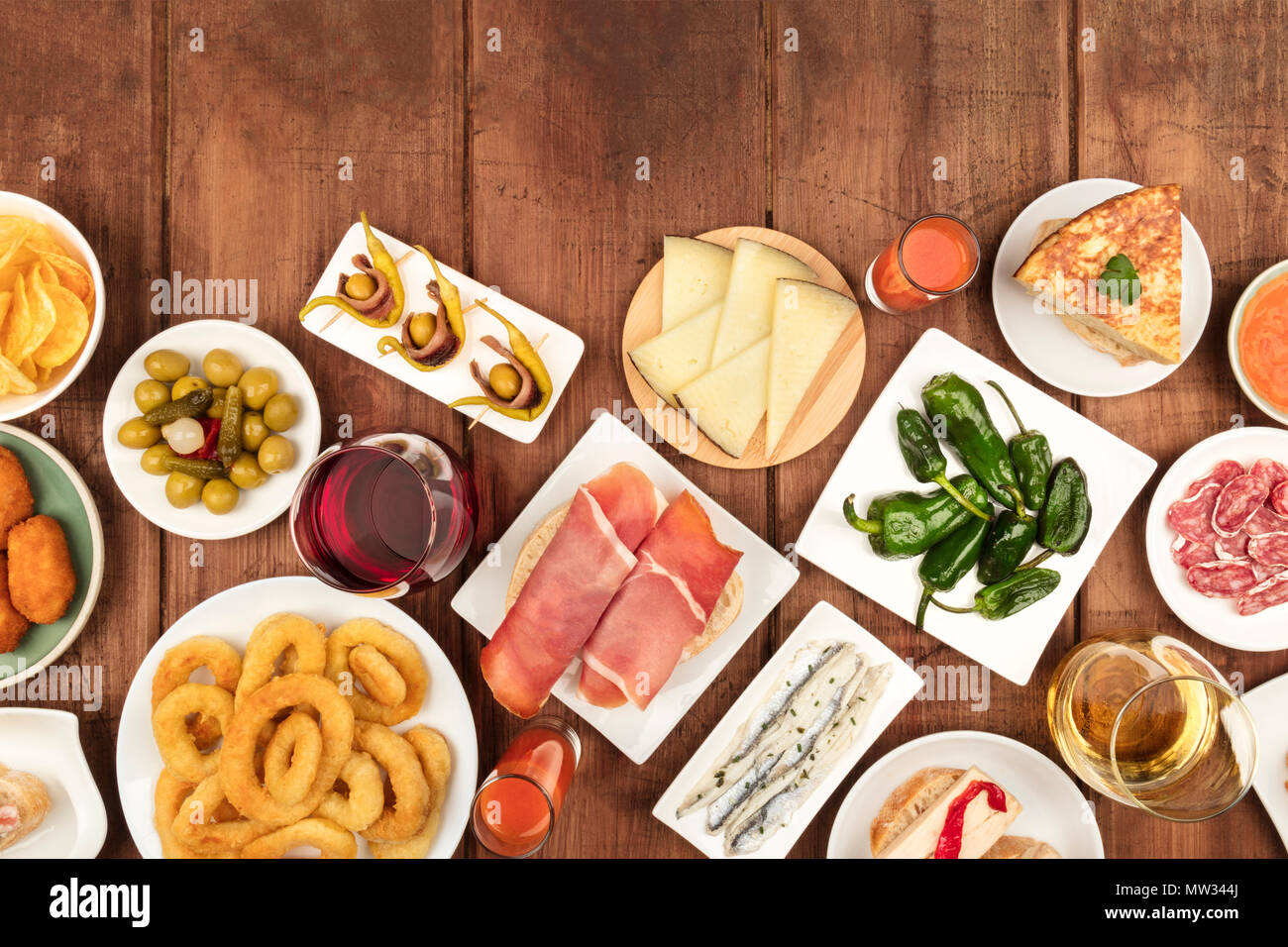 An overhead photo of an assortment of Spanish tapas food, shot from the top on a dark rustic background with copy space. Jamon, gazpacho, cheese, wine - Stock Image