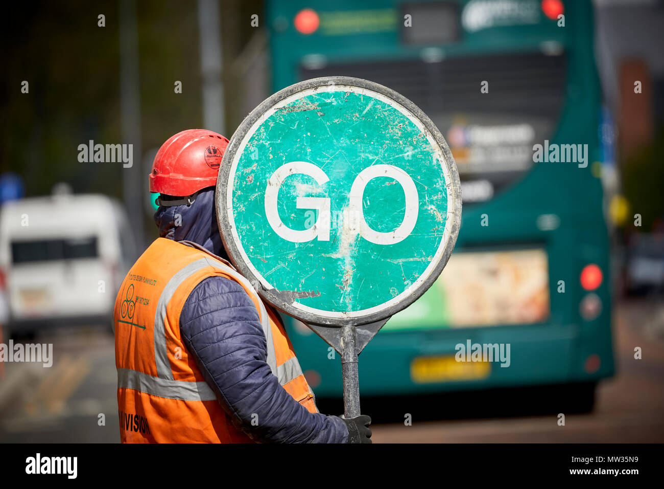 Construction worker using a manual traffic flow management using a stop go sign Oxford Road in Manchester - Stock Image