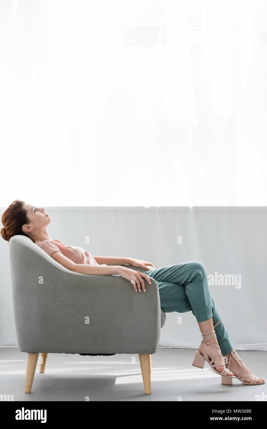 attractive young woman relaxing on comfy armchair at home - Stock Image