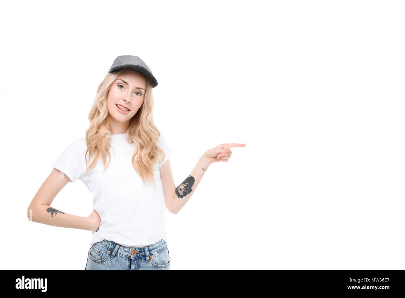 Half length shot of a young caucasian woman in casual clothes pointing to the side. - Stock Image