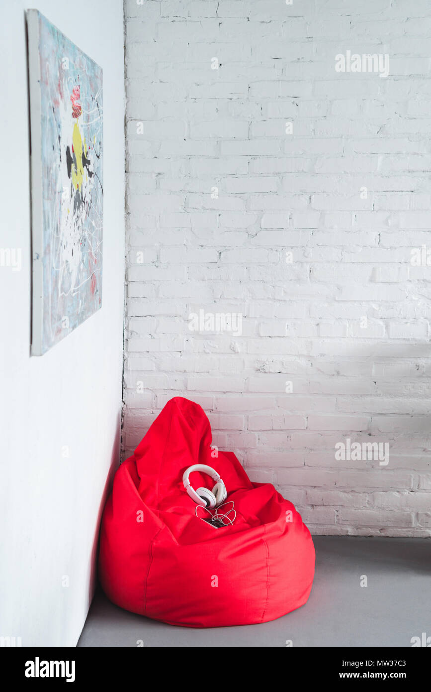 Smartphone with headphones on red bean bag by white wall - Stock Image